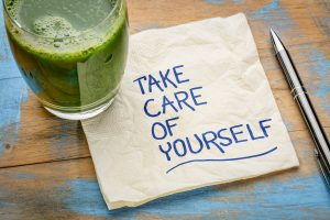 "Glass of Green Juice With A Napkin That Has ""Take Care of Yourself"" Written On It"