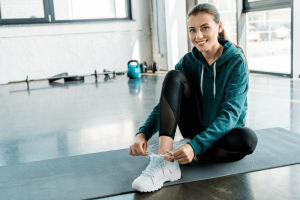 Exercise and Your Mental Health - Smiling young woman tying laces on training shoes while sitting on fitness mat.
