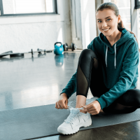 Exercise-and-Your-Mental-Health-Smiling-woman-tying-laces-on-training-shoes-while-sitting-on-fitness-mat
